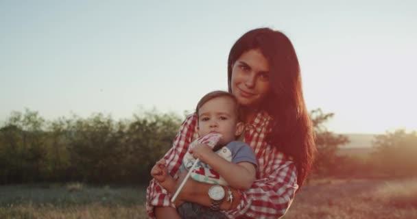 Closeup matka se svým synem před kamerou mají velký úsměv, radostné náladě, objímání tak roztomilé dítě v přírodě