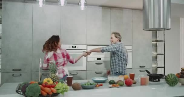Mature Couple Dacing Charismatic In The Kitchen While Preparing The