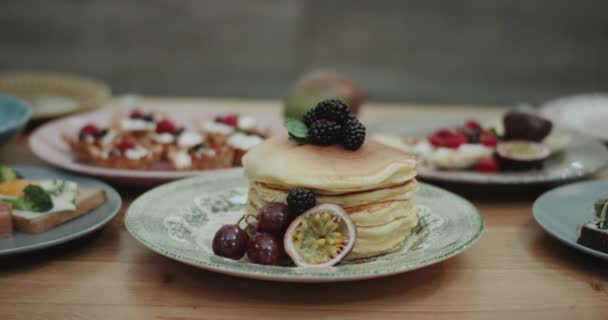 Someone in slow motion nicely pouring some honey on a neatly stacked pile of pancakes. shot on red epic. 4k . slow motions