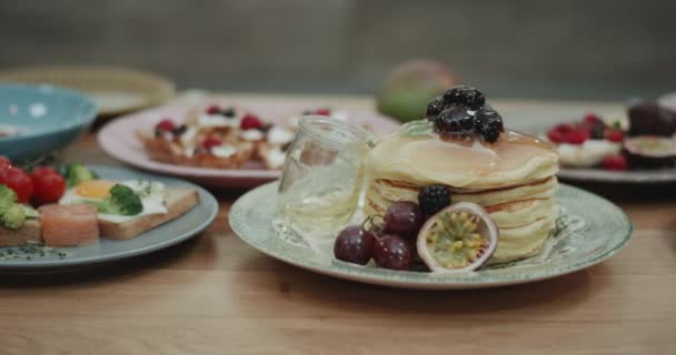 A nice shot of honey dripping down a stack of pancakes and other breakfast looking foods beside it.