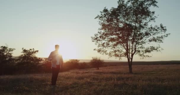 Krásný výhled na přírodní, charismatický mladík hrající uprostřed pole s malou raketou porazit míč