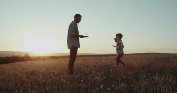Papa spielen mit seinem Sohn in der Natur auf Tennis, schönen Sonnenuntergang, verbringen gute Zeit zusammen.