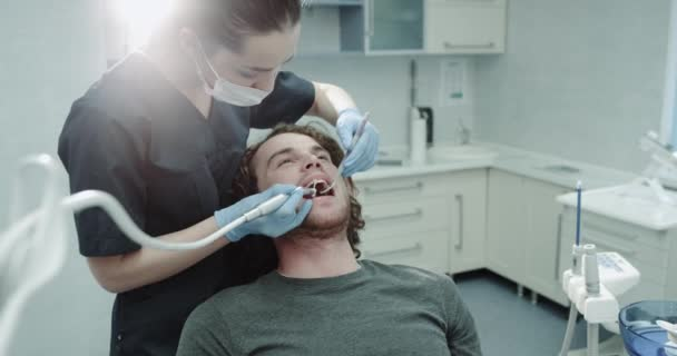Portrait of a woman dentis and her patient charismatic guy in a dental room have a oral hygiene procedure.
