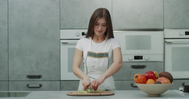 Charismatic young lady prepare a healthy dinner cut some vegetables , after she finish looks straight to the camera and smiling.
