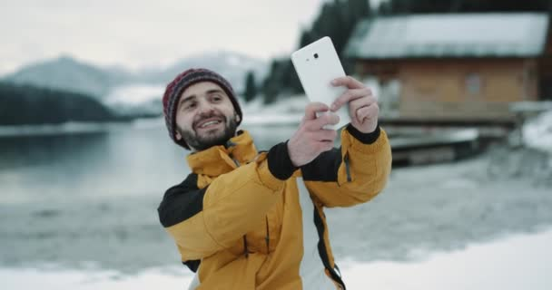 Charismatic young guy tourist take a funny selfie with a tablet in the middle of amazing landscape with a snowy lake and mountain , with green forest , closeup make photo in front of the camera , he