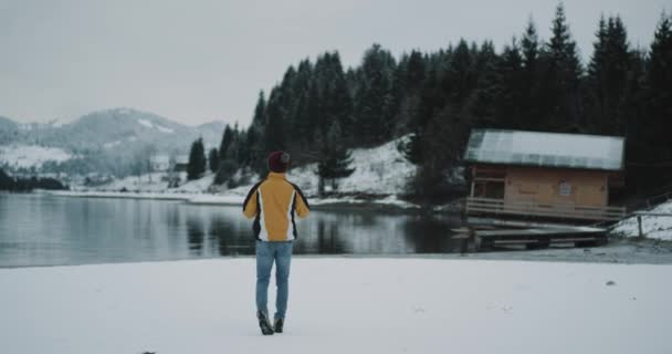 Tourist with a orange jacket in the middle of amazing blue lake with a snowy mountain and forest walking with a map and try to find his destination , he standing beside the shore of lake , background