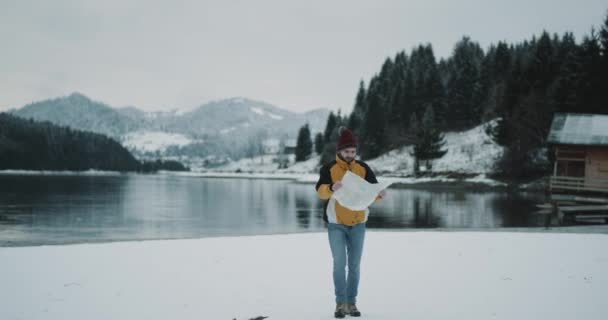 Charismatic young tourist with map walking around a snowy lake with a map he arrived in amazing landscape with snowy mountain and forest beside of a wooden house in a perfect winter day. 4k