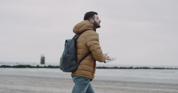 The tourist strolls along the seashore. Happy male tourist with backpack on shoulders exploring map while traveling .