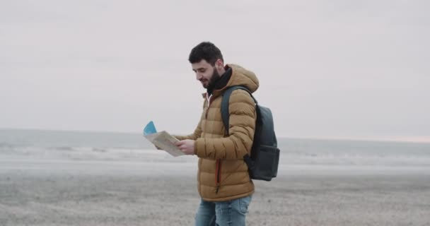 The tourist strolls along the seashore. Happy male tourist with backpack on shoulders exploring map while traveling . Shot on red epic. 4k