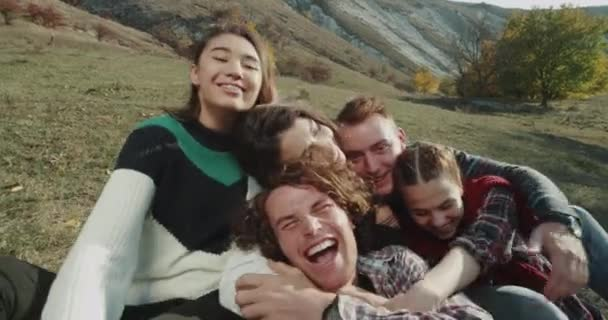 Very charismatics young people have a good time spending together they taking camera and making video with their faces , selfie time at nature.