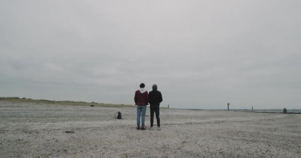 Two friends guys standing on the beach and have a meditation time , beside of a seashore. 4k
