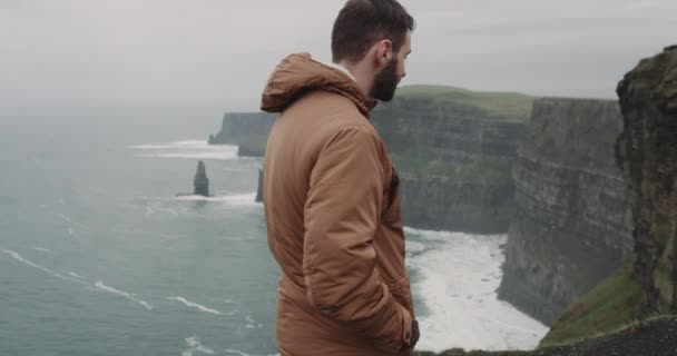 Happy tourist arrived in amazing place of Cliffs of Moher in Ireland he stand on the shore of Cliffs and feeling impressed of place and landscape background ocean view. slow motions