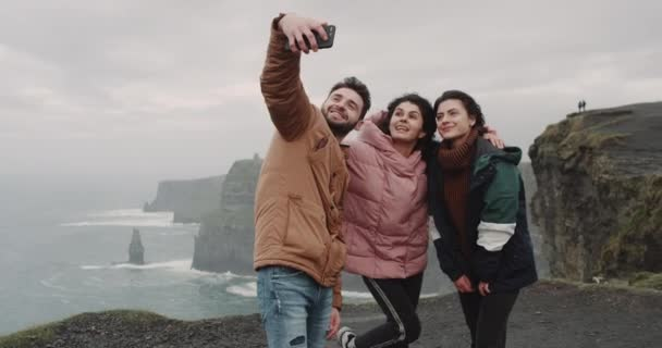 Closeup happy friends taking pictures in amazing place with beautiful landscape with a big Cliffs , they smiling large , they using a smartphone to take pictures. 4k