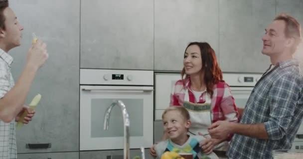 Táta a máma strávit den se svými dvěma syny v moderní kuchyni hrát legrační bubliny.