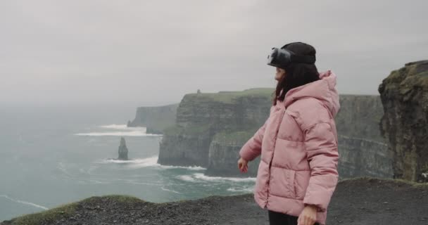 Happy lady using a VR , virtual reality glasses on the top of Cliffs and very charismatic playing with the emotion , she exploring the place using a VR , on very attractive landscape.