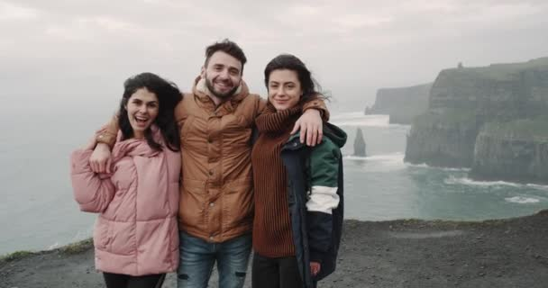 Happy three friends tourist posing in front of the camera to take pictures of memories in amazing place of Cliffs of moher with fantastic view of ocean. 4k