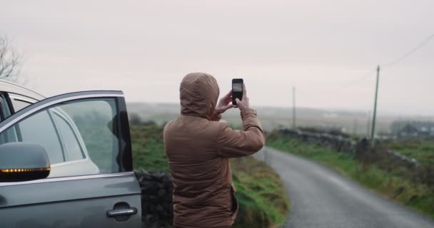 Young tourist stopped beside the road and take a picture of sunset in the evening , he travel on countryside in Ireland , amazing place with green field.
