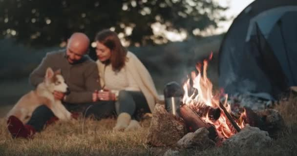 Amazing capturing video of a cute couple at the picnic beside of campfire spending a romantic time together with their husky dog playing in the evening. 4k