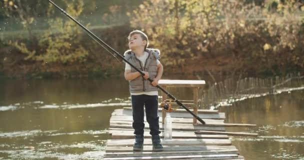 Tři roky starý brachu chytat ryby s velkým rybářským prutem na slunečný den on stál na mostě