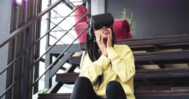 African young woman very impressed playing with a virtual reality glasses in a modern office , she sitting down on the stairs, beside a big window.