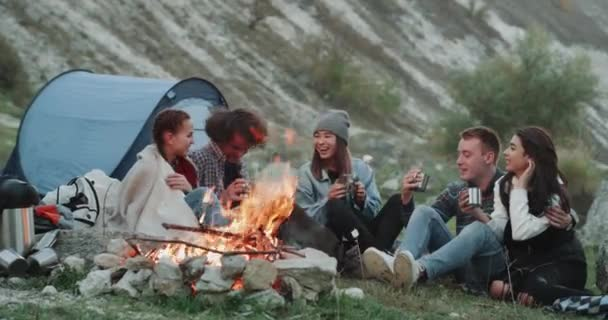 Smiling charismatic friends different races at camping , sitting beside a bonfire and drinking some hot drinks from metallic cups and spending a amazing time together.