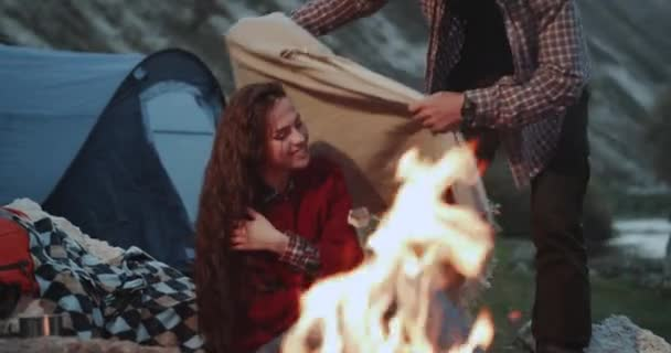 Young charismatic couple in the middle of evening at campfire spending lovely time together, taking a blanket and happy standing eat a marshmallows. 4k