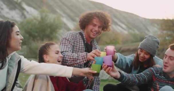 Closeup teens at camping have a good time , drinking some drinks from plastic cups and sitting around of campfire