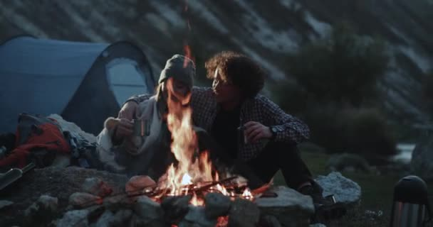 Closeup amazing campfire beautiful couple drinks some hot drinks hugging each other , and spending romantic time together.