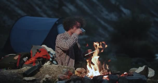 Charismatic curly hair young guy at camping beside the tent sitting beside of campfire and drinking some tea holding a tablet.