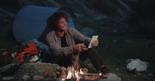 Young very charismatic man have a chat using a tablet in the middle of mountain beside a tent in the night , he speaks and smiling at same time.