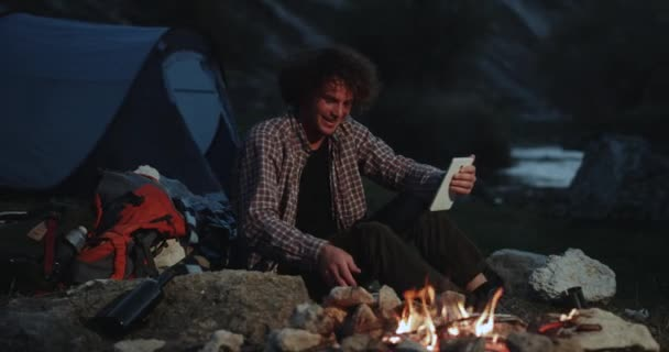 Chat time using a tablet in the middle of mountain at camping young guy have a great conversation , in the middle of night beside a campfire.