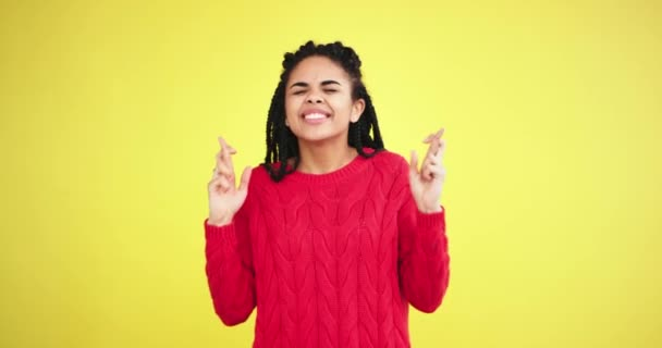 African young lady in a red sweater very charismatic playing in front of the camera in a studio with yellow background wall , crossing fingers and praying for something then very happy and enjoying
