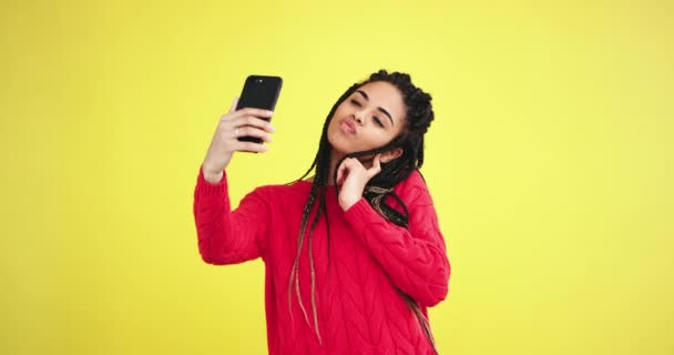 Charismatic multi ethnic lady in the studio with a yellow background wall taking selfies with her smartphone have a large smile with a white teeth she posing at the same take photo in front of the