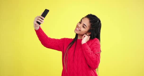 .Pretty african lady in a red sweater in the studio with a yellow background wall taking photo with smartphone in front of the camera she charismatic posing and smiling large.