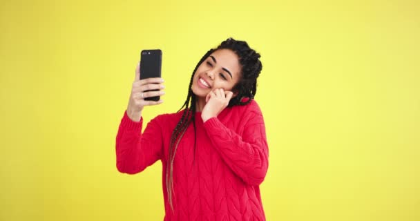 Amazing african lady take a pretty selfie with her smartphone in a yellow background wall in the studio.