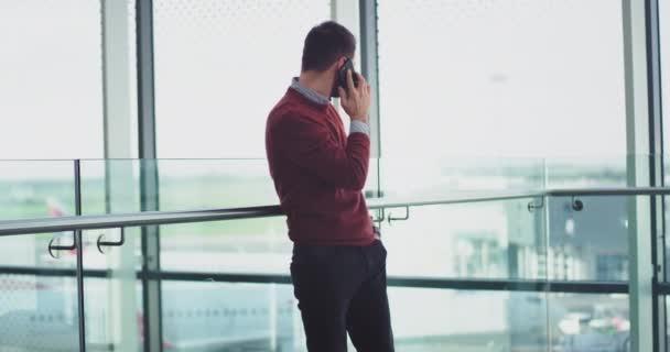 junger Mann, Büroangestellter am Telefon, führt ein Gespräch, das er neben einem großen Fenster in einem modernen Gebäude führt