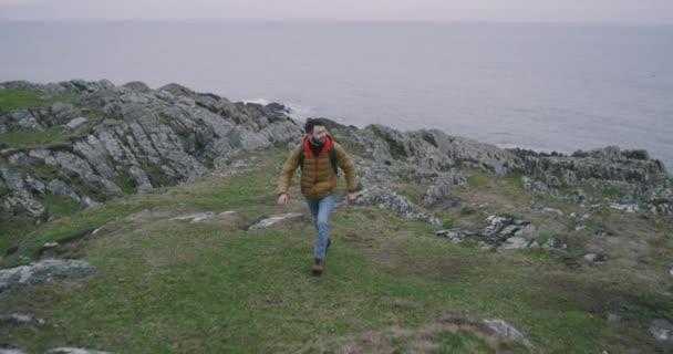 In the middle of Ireland walking tourist with a bag exploring the mountain he arrived in amazing place with a ocean view