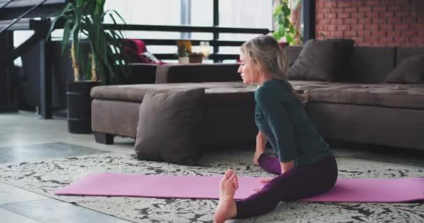 Fegyver egyensúly gyakorlatok szőke nő gyakorló a reggeli jóga életmód otthon a nappaliban, a rózsaszín szőnyeg, kap egy jó jóga meditáció-egészség-test. 4k