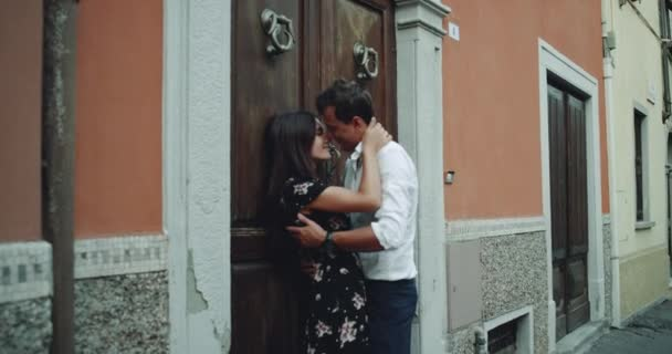 Young lady and man sensuality hugging each other beside of a old house , in the middle of a old small street in Italy.