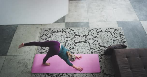 Attractive lady does yoga poses in the morning in the modern loft design from the top capturing video , she get energy for all day.