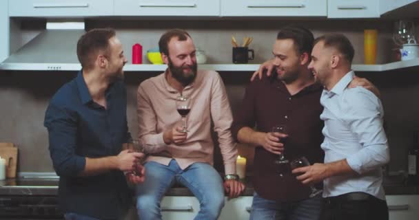Happy and charismatic young guys at home have a good time together drinking wine and feeling great , multi ethnic group of people.