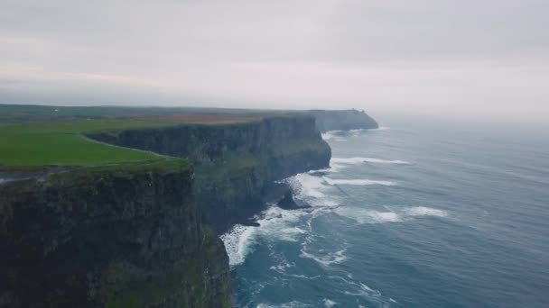 Green fields and amazing view of Cliffs of moher taking video using a drone from the air , beautiful landscape around.