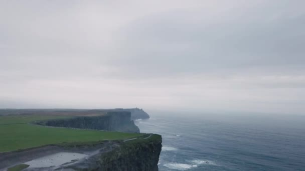 Drone video capturing tourist on the top of amazing stones view cliffs of moher , traveling people around visiting the place.