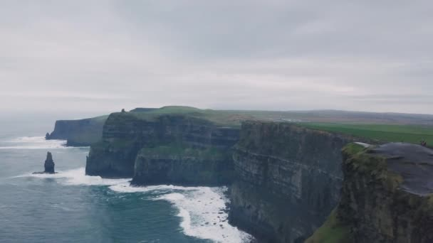 In a beautiful landscape view popular place tourist visiting a beautiful cliffs of moher capturing video from the air with drone.