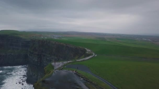 Drone capturing video from the air of amazing tourist place cliffs of moher , tourist exploring the landscape.