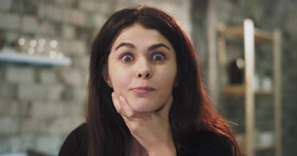 Porträt einer charismatischen Dame, die direkt in die Kamera schaut und eine gute Idee in ihrem Kopf hat, gestikulierend mit den Händen in die Kamera, sie hat eine weiße Zahnspange aus Keramik