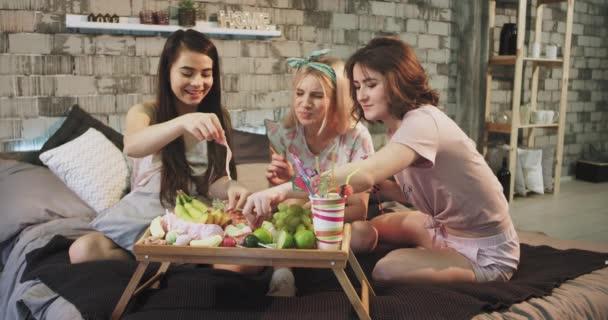 Szép látszó hölgyek a kamera előtt van egy színes fél otthon egy modern hálószoba étkezési zselét, és mosolyogva nagy, fárasztó pizsama