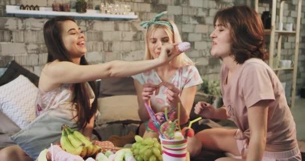 Egy aranyos női tinédzser pizsama egy édes buli az ágyban, hogy eszik édességet, és élvezi az időt kiadások együtt