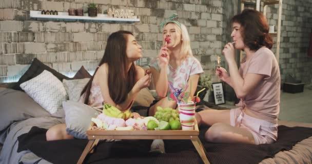 Vicces tinédzser lányok egy sleepover éjszaka több édesség, esznek nyalókák és az érzés nagy együtt. 4k