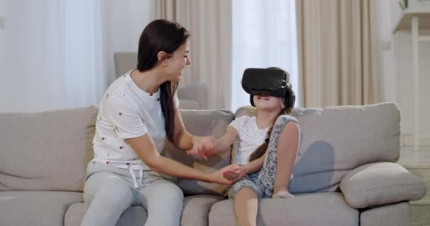Mature mother with her small daughter exploring the virtual world together using a virtual reality glasses, they sitting on the sofa in a large living room